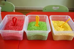 Recipiente sensoriale per i bambini con riso colourful sulla tavola rossa fotografia stock libera da diritti