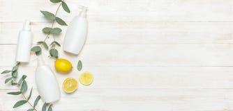 Recipientes cosméticos da garrafa dos brancos, eucalipto fresco do limão no espaço colocado liso de madeira branco da cópia da op fotografia de stock royalty free