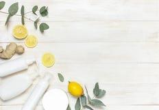 Recipientes cosméticos da garrafa dos brancos, limão fresco, raiz do gengibre, eucalipto no espaço colocado liso de madeira branc fotos de stock royalty free