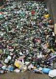 Recipientes de vidro empilhados em reciclar o centro Imagens de Stock