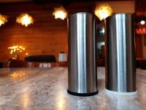 Recipientes do metal da especiaria em uma superfície branca Frascos da especiaria Material de cozinha na tabela, fundo obscuro Vi imagens de stock royalty free