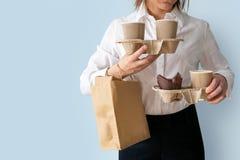 Recipientes fêmeas do café da terra arrendada, recipientes do withfood do saco de papel Entrega do alimento e do café imagens de stock royalty free
