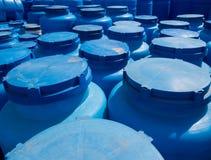 Recipientes plásticos azuis para o armazenamento dos líquidos na área de armazenamento Foto de Stock Royalty Free