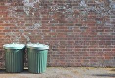Recipienti dei rifiuti di cestino delle pattumiere fuori contro il muro di mattoni Fotografie Stock Libere da Diritti