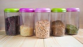Recipienti di plastica con i cereali Prodotti domestici di stoccaggio Immagine Stock