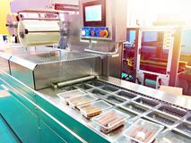 Recipienti di plastica con le salsiccie sul trasportatore alla fabbrica dell'alimento immagini stock