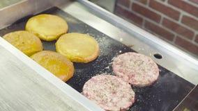 Recipienti ed hamburger che friggono su una griglia archivi video