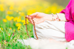 Recitation of mantras holding the mala during a yoga practice Stock Photos