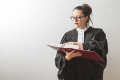 Reciting the law. Thirty something brunette woman wearing a canadian lawyer toga, reciting from a red criminal law book Stock Images
