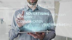 Reclame, marketing, bevordering, verkoop, bedrijfsdiewoordwolk als hologram wordt gemaakt op gebruikte tablet door de gebaarde me stock videobeelden