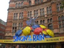 Reclame van 'het zingen in de regen 'met kleurrijke paraplu's stock afbeelding