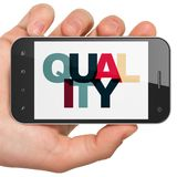 Reclameconcept: Handholding Smartphone met Kwaliteit op vertoning Stock Foto