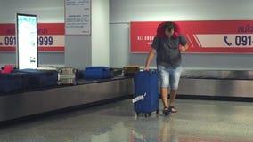 Reclamo di bagaglio dell'aeroporto Il viaggiatore del giovane prende i suoi bagagli dal trasportatore 3840x2160 stock footage