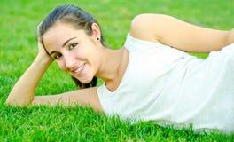 Reclinación adolescente hermosa sobre hierba Foto de archivo libre de regalías