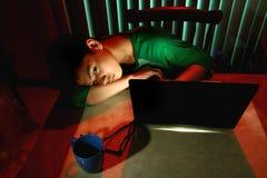Reclinación adolescente joven delante de un ordenador portátil Imagen de archivo