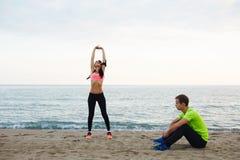 Reclinación atlética de los pares jovenes después del entrenamiento al aire libre Fotografía de archivo