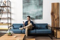 Reclinación barbuda del individuo joven feliz con el teléfono móvil en sala de estar Fotografía de archivo libre de regalías