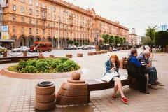 Reclinación de la gente, sentándose en banco en la calle de Lenin foto de archivo