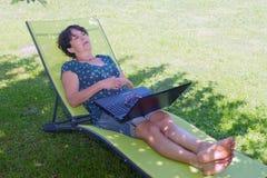 Reclinación de relajación de la mujer madura feliz sobre la silla de cubierta en jardín fotografía de archivo