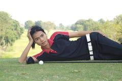Reclinación femenina del jugador de golf Foto de archivo libre de regalías