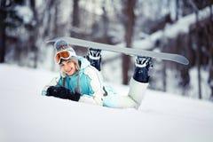 Reclinación femenina joven del snowboarder Imagen de archivo libre de regalías