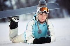 Reclinación femenina joven del snowboarder Foto de archivo libre de regalías