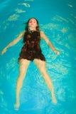 Reclinación flotante de la mujer en agua de la piscina Foto de archivo libre de regalías