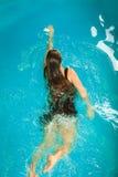 Reclinación flotante de la mujer en agua de la piscina Imagen de archivo