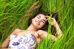 Reclinación joven y día de la mujer que se acuestan en hierba verde Imágenes de archivo libres de regalías