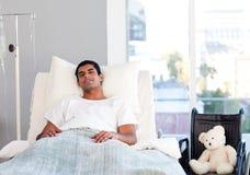Reclinación paciente hispánica en cama Foto de archivo