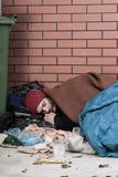 Reclinación sin hogar sobre el pavimento foto de archivo libre de regalías