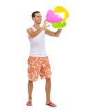 Reclinación sobre el hombre de las vacaciones que juega con la bola de playa Fotografía de archivo libre de regalías