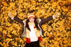 Reclinación de mentira de la mujer del otoño sobre las hojas Foto de archivo libre de regalías