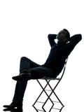 Reclinación que se sienta del hombre mirando para arriba la silueta integral Imagen de archivo libre de regalías