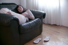 Reclinación sobre el sofá Fotos de archivo