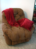 Recliner Chair. Shot of a brown recliner chair with a deep red throw and a couple pillows of the same color royalty free stock image