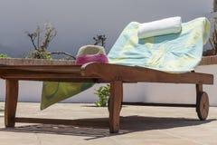 Recliner de madera del sol ocupado por la toalla y el sombrero El días de fiesta Fotografía de archivo
