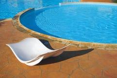 Recliners por la piscina en la configuración tropical Fotos de archivo libres de regalías