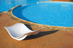 Recliners by swimming pool in tropical setting Royalty Free Stock Photos