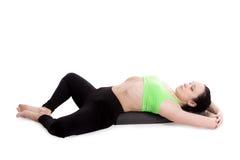 Reclining Bound Angle yoga Pose. Sporty girl on white background resting in Reclining Bound Angle yoga Pose, Supta Baddha Konasana, restorative, relaxing asana Royalty Free Stock Image