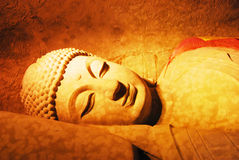 Reclining buddha. This Grottoes Reclining Buddha statue is located in Xinchang Buddha Temple, is cut from the granite mountain formed Stock Images