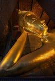 Reclining Buddha gold statue face Stock Photo
