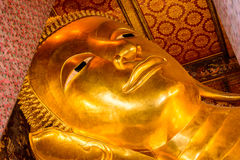 The reclining Buddha gold statue face in Bangkok, Thailand. Royalty Free Stock Image