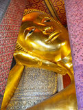 Reclining buddha gold statue face. Temple of the Reclining Buddha (Wat Pho), in Bangkok, Thailand. Reclining buddha gold statue face Royalty Free Stock Images