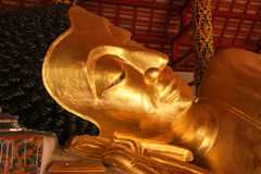 Reclining Buddha gold statue face in Thai temple - Lampang Province , THAILAND. Royalty Free Stock Photo
