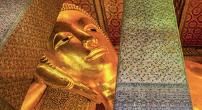 Reclining Buddha gold statue face Stock Photography