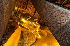 Reclining Buddha gold statue face Stock Images