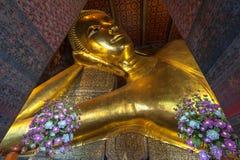 Reclining Buddha gold statue face. Wat Pho. Bangkok, Thailand royalty free stock images