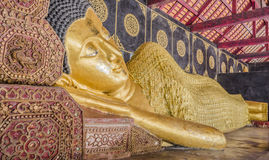Reclining Buddha gold statue in temple of Thailand. Royalty Free Stock Images