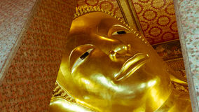 Reclining Buddha gold statue and thai art architecture Stock Photos